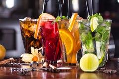 薄荷的mojito鸡尾酒,橙色鸡尾酒,在玻璃玻璃的草莓鸡尾酒与秸杆 酒吧辅助部件:振动器 免版税图库摄影
