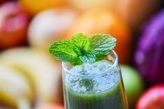 薄荷茶-在新鲜蔬菜汁圆滑的人和夏天果子背景的绿色薄荷的叶子 库存照片