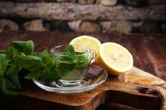 薄菏杯薄荷的茶和叶子在桌上的 免版税图库摄影