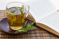薄菏绿茶和叶子在一个玻璃杯子的有书的 库存图片