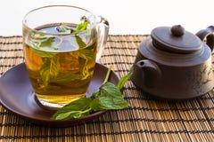 薄菏绿茶和叶子在一个玻璃杯子的 免版税图库摄影