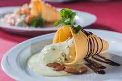 薄酥饼锥体用液体巧克力和杏仁 免版税库存图片