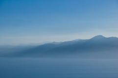 薄雾的山和海运。 库存照片