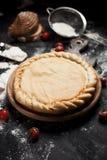 薄饼、面粉和蕃茄的准备在一张黑木桌上的一个圆的木板 库存图片
