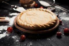 薄饼、面粉和蕃茄的准备在一张黑木桌上的一个圆的木板 免版税库存照片