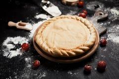 薄饼、面粉和蕃茄的准备在一张黑木桌上的一个圆的木板 免版税图库摄影
