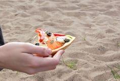 薄饼在手中在岸的沙子背景 库存图片