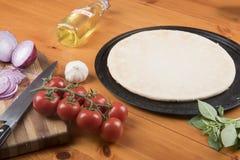 薄饼基地围拢用大蒜、蕃茄、葱、橄榄油和蓬蒿 库存照片