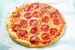 薄饼用乳酪和意大利辣味香肠蓝色表面上 免版税库存照片