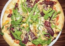 薄饼用意大利辣味香肠和蒜味咸腊肠在一张土气木桌上 图库摄影