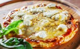 薄饼用无盐干酪乳酪、蕃茄、胡椒、香料和新鲜的蓬蒿 意大利薄饼 在木选项的比萨马尔盖里塔或玛格丽塔 免版税库存图片