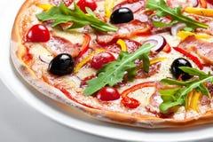 薄饼用烟肉、橄榄和红辣椒在一块白色板材 免版税图库摄影
