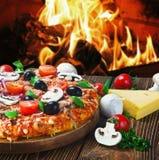 薄饼用蘑菇和乳酪在木桌上服务 免版税库存照片