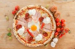 薄饼用鸡蛋、烟肉、火腿、酸奶油、蒜味咸腊肠和意大利辣味香肠-顶视图 库存照片