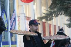 """薄饼送货人带来在手上的薄饼在佩尔尼克,保加利亚街道†""""2008年1月26日 免版税库存图片"""