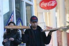 """薄饼送货人带来在手上的薄饼在佩尔尼克,保加利亚街道†""""2008年1月26日 库存照片"""