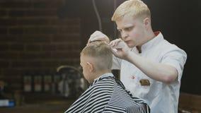 薄饼 时髦的小男孩做理发在理发师 一个美丽的男孩得到与一位时髦的美发师的理发 股票录像