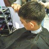 薄饼 理发少年,大师特写镜头做在理发店的头发理发 免版税库存照片