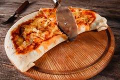 薄饼calzone用在木盛肉盘的轮子切开了 库存照片