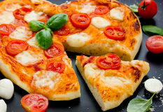 薄饼Margherita塑造了心脏用西红柿,无盐干酪a 库存照片