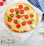 薄饼Margherita用乳酪和蕃茄在一个木板 库存图片
