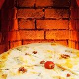 薄饼quatro formaggi和热的砖烤箱 免版税库存图片