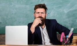 薪水关注细节 老师集中了听与注意的有胡子的成熟男校长 老师听 免版税库存照片