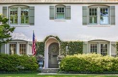藤对白色被绘的砖房子的报道的入口有被成拱形的前门的和花圈和被成拱形的窗口与绿色快门-土地 免版税图库摄影