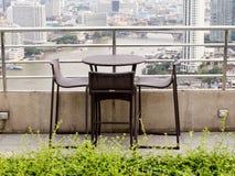 藤条与站立反对ter的两把凳子椅子的一张桌 免版税库存照片