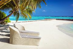 藤条在马尔代夫海滩的太阳懒人 免版税库存照片