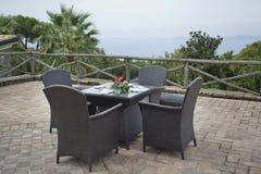藤条室外庭院被编织的棕色桌和椅子 免版税库存图片