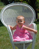 藤椅的女婴 免版税图库摄影