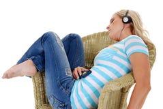 藤椅的妇女听到音乐的通过耳机 免版税库存照片