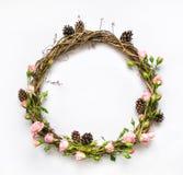 藤欢乐花圈与装饰玫瑰、叶子和锥体的 平的位置,顶视图 免版税库存图片