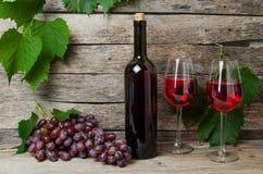 藤瓶酒和两块玻璃用红葡萄酒 免版税图库摄影