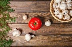 蘑菇和蕃茄在一张木桌上 免版税图库摄影