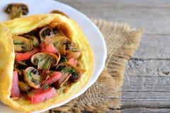 蘑菇和蕃茄煎蛋卷 自创煎蛋卷充塞用油煎的蘑菇、新鲜的蕃茄和莳萝绿色在板材 免版税图库摄影
