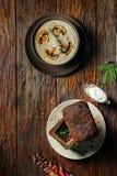 蘑菇奶油色在面包的汤装饰用切的蘑菇和汤在黑暗的木桌上 库存图片