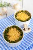 蘑菇热的盘,鸡在乳脂状的调味汁调味酱烘烤了,在乳酪外壳下,绿色装饰,在小陶瓷碗 免版税库存照片