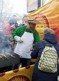 蘑菇衣服的一个人倒蘑菇汤在一个民间节日 库存图片