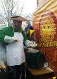 蘑菇衣服的一个人倒蘑菇汤在一个民间节日 图库摄影