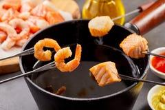 蘸新鲜的三文鱼和大虾入一个热的涮制菜肴 库存图片