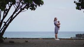 虔诚拥抱母亲和的婴孩,花费接合质量时间观察明亮的蓝色cloudscape 殷勤育儿 股票视频