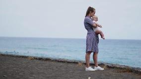 虔诚拥抱母亲和的婴孩,花费接合质量时间观察明亮的蓝色cloudscape 殷勤育儿 股票录像