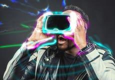 戴虚拟现实使用Google/VR眼镜的年轻人 库存照片