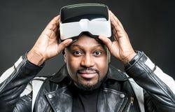 戴虚拟现实使用Google/VR眼镜的年轻人 图库摄影