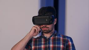 虚拟现实玻璃的严肃的年轻人谈话在电话 免版税库存照片