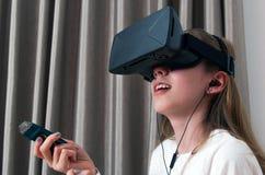 虚拟现实的耳机和查寻声音的设备的女孩和 免版税库存图片