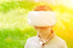 虚拟现实盔甲微笑的男孩在绿草背景  免版税库存图片