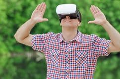 虚拟现实盔甲的人以自然为背景的 举起手来 免版税库存图片
